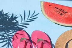 Summer vacation concept Flay lay Fresh watermelon Flip flops Straw hat light blue background Top view Copy space Tropical leaf sh stock image