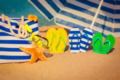 Summer vacation concept. Flip-flops, beach bag and funny starfish on the sand. Summer vacation concept Royalty Free Stock Images