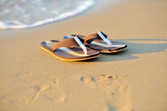 Flip flops on a sandy ocean beach Royalty Free Stock Image