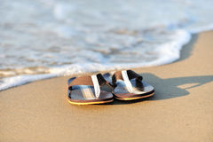 Flip flops on a sandy ocean beach Stock Images