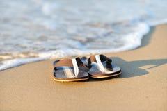 Flip flops on a sandy ocean beach Stock Images