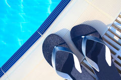Summer vacation concept. Flipflops at the edge of the swimming p Royalty Free Stock Images