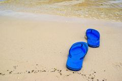 Summer vacation concept--Flipflops on a sandy ocean beach. Stock Photo