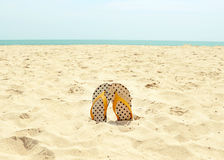 Summer vacation concept. Flipflops on a sandy ocean beach. Royalty Free Stock Photo