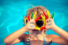 Summer vacation concept. Funny child with drawing smiley on hands in swimming pool. Summer vacation concept