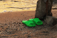 Summer vacation concept. green Flipflops on a sandy ocean beach. The sunset, the beach, the remains of the old pier Royalty Free Stock Photos