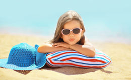 Summer vacation concept, joyful child. In sunglasses and hat having fun lying on the sand coast sea royalty free stock photography
