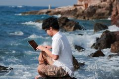 Summer vacation concept. Lifestyle Asian man with laptop relaxing at blue sea shore. Summer vacation concept. Lifestyle Asian man with laptop relaxing at blue Royalty Free Stock Photos