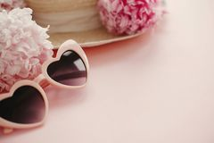 Summer vacation concept. Stylish girly pink retro sunglasses, white and pink peonies, straw hat on pastel pink paper with copy. Space. Hello spring concept stock image