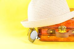 Summer vacation concept. Bright yellow background with hat, sun glasses and bag suitcase Royalty Free Stock Photos