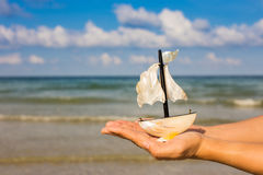 Summer vacation concept. Toy sailing boat in hands on the water Royalty Free Stock Photos