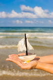 Summer vacation concept. Toy sailing boat in hands on the water Stock Photography