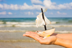 Summer vacation concept. Toy sailing boat in hands on the water Royalty Free Stock Images