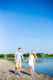 Summer vacation concept - young couple walking on the beach Stock Images