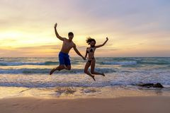 Summer Vacation.  Couple jumping holding hands on tropical on the beach sunset time in holiday trips.  Honeymoon holidays people r. Elaxing together on summer royalty free stock photos