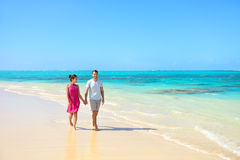 Summer vacation couple walking on beach landscape. Young adults relaxing together enjoying their holidays in perfect getaway in sunny tropical destination with Royalty Free Stock Photos