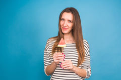 Summer, vacation, diet and vegans concept - Beautiful smiling young woman holding watermelon slice on stick Stock Image