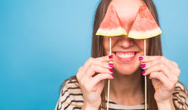 Summer, vacation, diet and vegans concept - Beautiful smiling young woman holding watermelon slice on stick.  Stock Photos