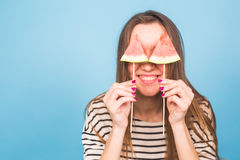 Summer, vacation, diet and vegans concept - Beautiful smiling young woman holding watermelon slice on stick.  Stock Photo