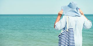 An elderly woman in a hat looks at the sea. Summer vacation. stock photography