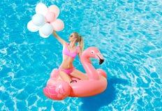 Woman in bikini on the inflatable mattress in the swimming pool. Stock Photos