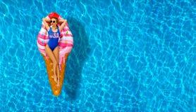 Woman in bikini on the inflatable mattress in the swimming pool. Stock Image
