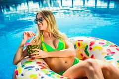 Woman in bikini on the inflatable mattress in the swimming pool. Summer Vacation. Enjoying suntan Woman in bikini on the inflatable mattress in the swimming stock images