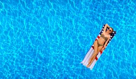Woman in bikini on the inflatable mattress in the swimming pool. Royalty Free Stock Image