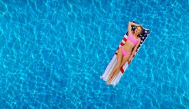 Woman in bikini on the inflatable mattress in the swimming pool. stock photos