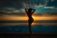 Summer Vacation. Silhouette of beauty dancing woman on sunset near the pool with ocean view. Royalty Free Stock Image