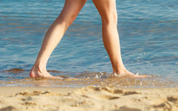 Summer vacation. Female feet on the beach. Vacation. Closeup of female feet. Woman walking alone on the empty beach. Young woman relaxing on the sea coast Royalty Free Stock Images