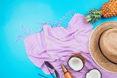 Summer vacation flatlay with straw hat, pink scarf, pineapple, coconut, body oil and glasses royalty free stock image