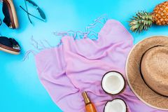 Summer vacation flatlay with straw hat, pink scarf, pineapple, coconut, body oil, sandals. And sunglasses on blue Royalty Free Stock Image