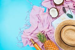 Summer vacation flatlay with straw hat, pink scarf, pineapple, coconut, body oil and glasses. Summer vacation flatlay with straw hat, pink scarf, pineapple Stock Images
