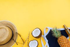 Summer vacation flatlay with straw hat, swimsuit, coconut halves, body oil and glasses. On yellow with copyspace stock image