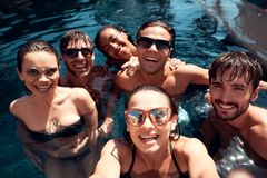 Summer vacation friends together at swimming pool party. Swimming pool party. Company of young people spend weekend in aquapark Stock Images