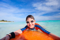 Summer vacation fun. Little boy on vacation having fun swimming on boogie board Royalty Free Stock Image