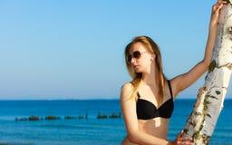 Summer vacation. Girl in bikini standing on beach Stock Photography