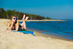 Summer vacation Girl in bikini sunbathing on beach. Summer vacation. Sexy girl in bikini sunbathing tanning on the beach. Young woman relaxing on the sea coast Stock Image