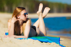 Summer vacation Girl in bikini sunbathing on beach. Summer vacation. Sexy girl in bikini sunbathing tanning on the beach. Young woman relaxing on the sea coast Stock Photography