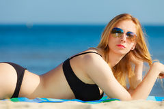Summer vacation Girl in bikini sunbathing on beach Stock Photo