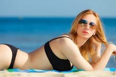 Summer vacation Girl in bikini sunbathing on beach Stock Photo