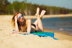 Summer vacation Girl in bikini sunbathing on beach Royalty Free Stock Photography