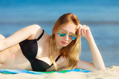 Summer vacation Girl in bikini sunbathing on beach Royalty Free Stock Image