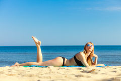 Summer vacation Girl in bikini sunbathing on beach Stock Images