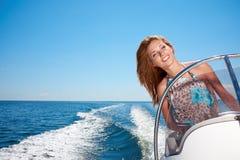 Summer vacation - girl driving a motor boat. Summer vacation - young girl driving a motor boat Royalty Free Stock Photo