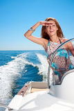 Summer vacation - girl driving a motor boat. Summer vacation - young girl driving a motor boat Stock Images
