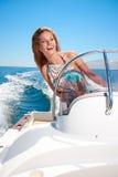 Summer vacation - girl driving a motor boat Stock Image