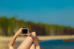 Summer vacation Girl with phone tanning on beach Royalty Free Stock Images