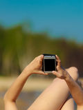 Summer vacation Girl with phone tanning on beach. Summer vacation. Closeup of female hands. Girl sunbathing tanning on the beach. Young woman relaxing with Royalty Free Stock Photography